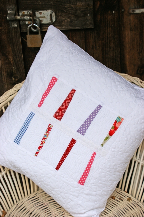 A pure white strippy, scrappy quilted cushion