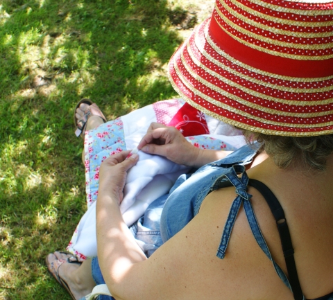 sitting in the dappled shade of the apple trees, binding a quilt