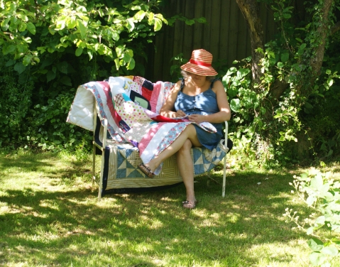 Hand-stitching the binding of a king-sized memory quilt, in the dappled shade of the apple trees.